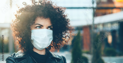 Foto Curly haired caucasian woman wearing an anti flu mask while posing outside on fr