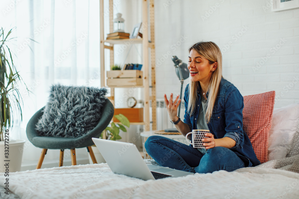 Fototapeta Young woman sitting on bed in bedroom and having video call via laptop