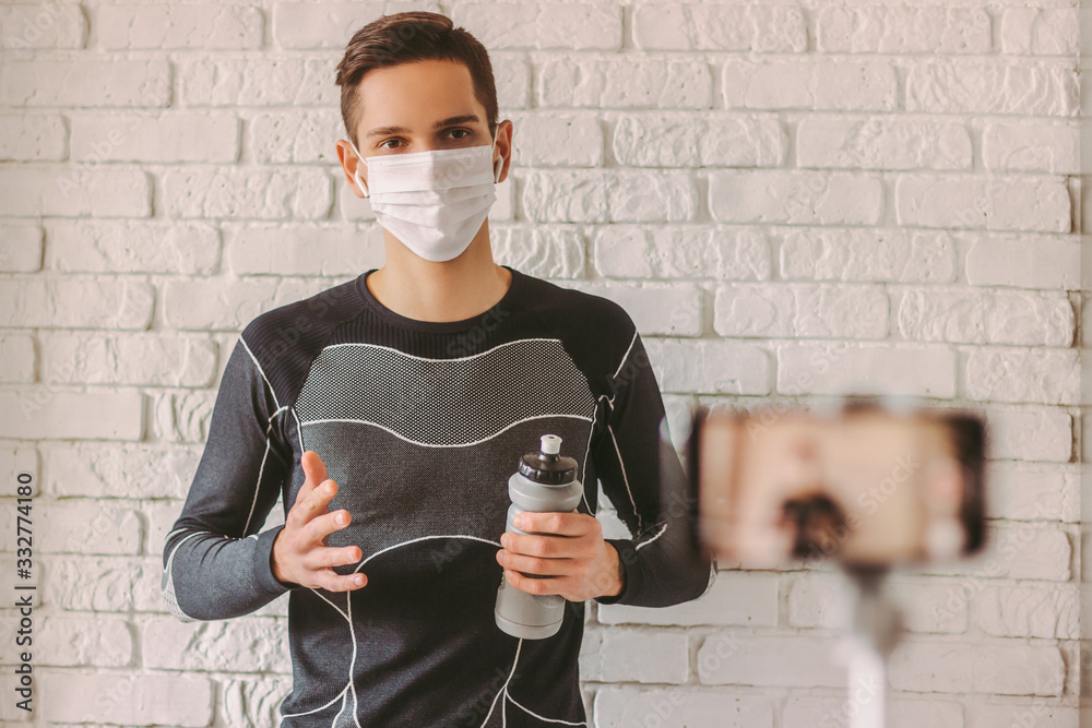 Fototapeta Confident sports man in protective face mask recording video on phone for his blog. Online workout classes with young professional fitness instructor in protective face mask. COVID-19 home quarantine