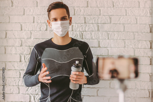 Fototapeta Confident sports man in protective face mask recording video on phone for his blog. Online workout classes with young professional fitness instructor in protective face mask. COVID-19 home quarantine obraz