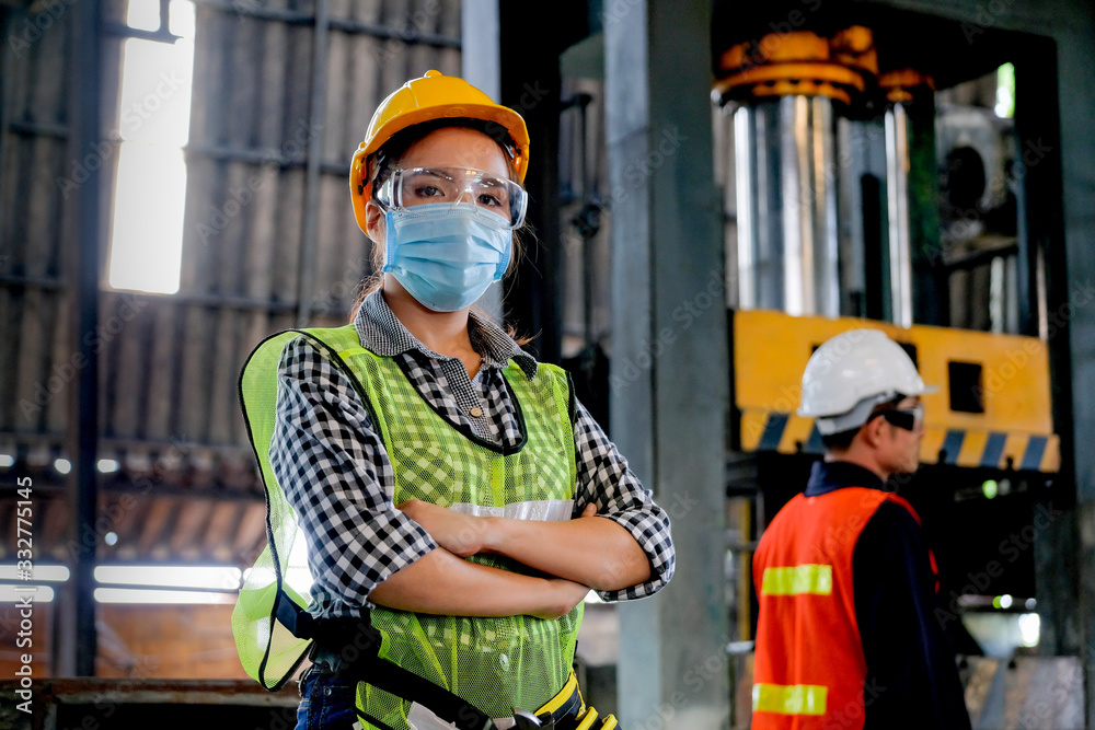 Fototapeta Factory woman engineer worker or technician with hygienic mask stand with confident action with her co-worker in workplace. Concept of good industrial system for better manufacture business.