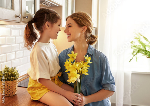 child daughter   gives mother   bouquet of flowers to narcissus