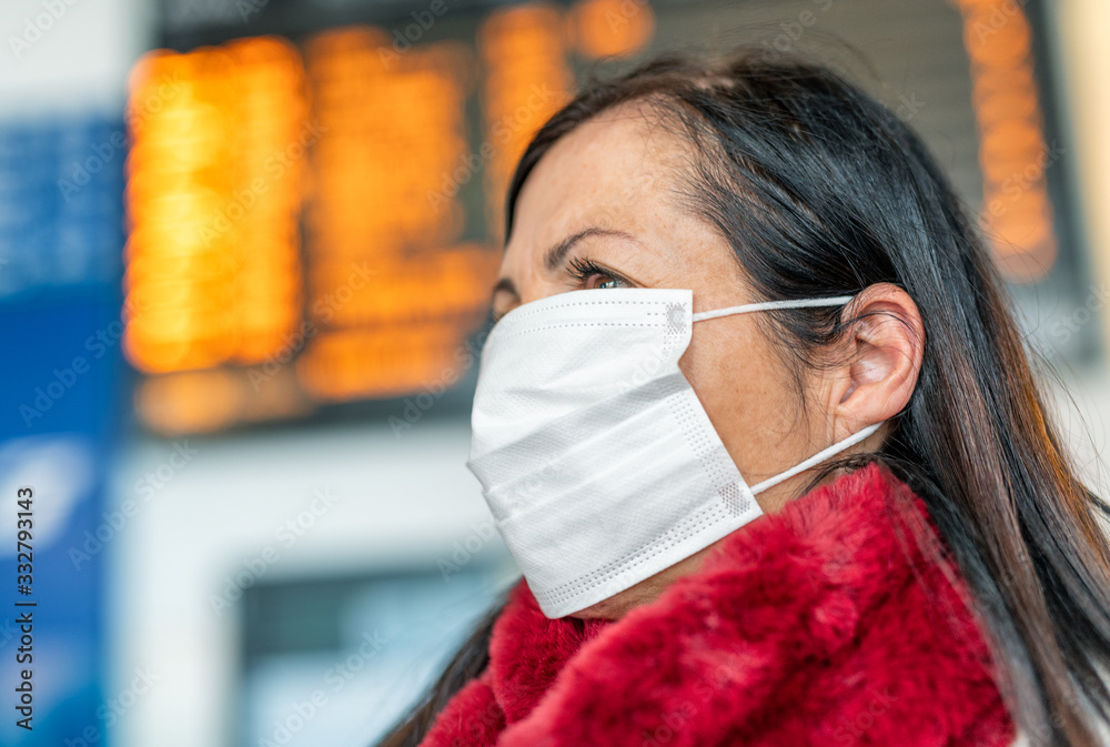 Fototapeta Woman wearing protective mask at the airport. Coronavirus outbreak prevention protection concept