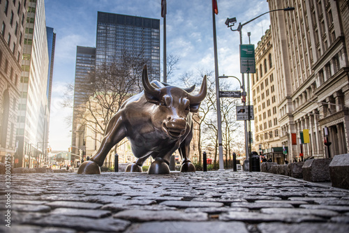 NEW YORK CITY - MARCH 24, 2020: Charging Bull sculpture on March 24, 2020 on empty streets of  New York City during Corona virus Epidemic.