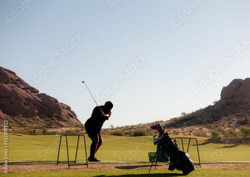 Fototapety, obrazy: Anonymous man alone practicing golf swing on driving range.