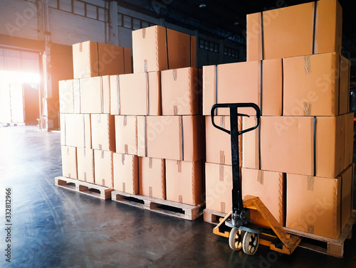 Leinwand Poster Interior of warehouse storage, Stack of shipment boxes on pallets and hand pallet truck, Warehouse industry delivery shipment goods, logistics and transportation