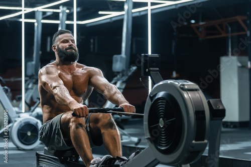 Fototapeta Young strong bearded bodybuilder doing low cable pulley row seated
