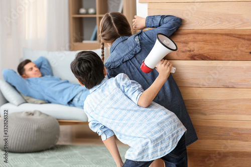 Children playing a prank on their father at home Wallpaper Mural