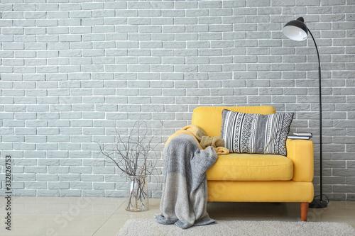 Obraz Armchair and lamp near brick wall - fototapety do salonu