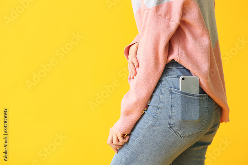Fotomural Beautiful young woman with mobile phone in pocket on color background, closeup