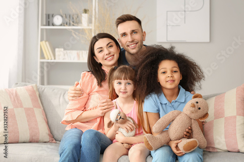 Happy couple with little adopted children at home Canvas Print