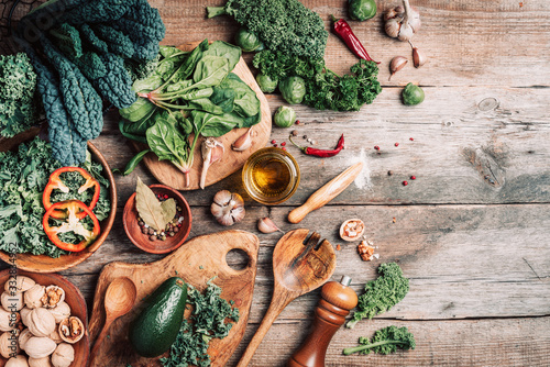 Obraz Orgnic healthy vegan food cooking ingredients. Top view. Copy space. Green vegetables, seeds, avocado, nuts, kale, spices, salt, wooden utensils on wood background. Clean eating food, zero waste - fototapety do salonu