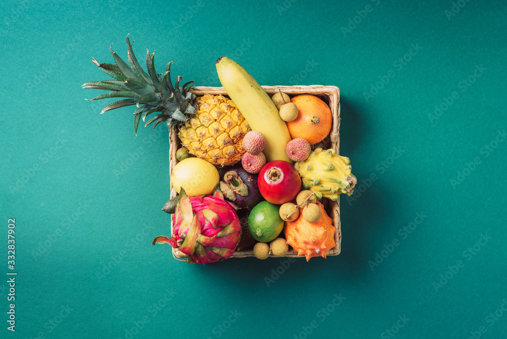 Fototapeta Tropical fruits on green background. Rattan box full of exotic thailand fruits - pineapple, pitahaya, kiwano, african horned melon, tamarillo fruit, granadilla, feijoa, salak, snake fruits, maracuya