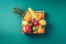 Tropical Fruits On Green Background. Rattan Box Full Of Exotic Thailand Fruits - Pineapple, Pitahaya, Kiwano, African Horned Melon, Tamarillo Fruit, Granadilla, Feijoa, Salak, Snake Fruits, Maracuya