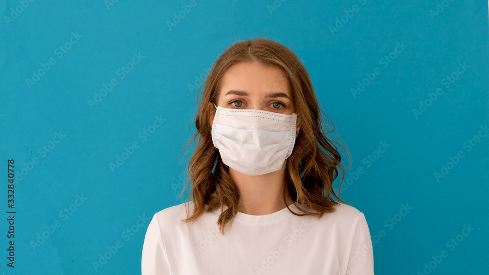 Fototapeta Woman putting on surgical mask for corona virus prevention on blue background