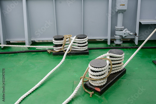 Photo Mooring bollard with a fixed rope on the ship.