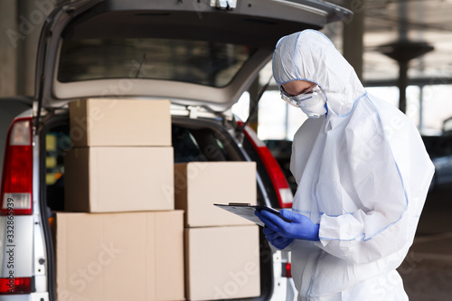 Obraz Danger business of trucking, delivering in virus protective suit - fototapety do salonu