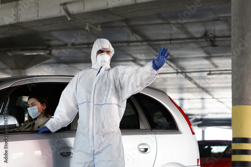 Man in hazmat showing stop sign for cars