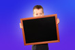Leinwandbild Motiv little boy of European appearance, a schoolboy, holds with two hands a black school board without text on a blue isolated background, concept of message, information