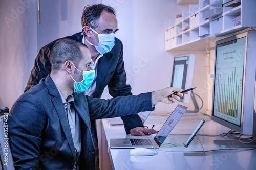 Obraz coleghi in ufficio controllano i dati in un monitor nel loro ufficio - fototapety do salonu