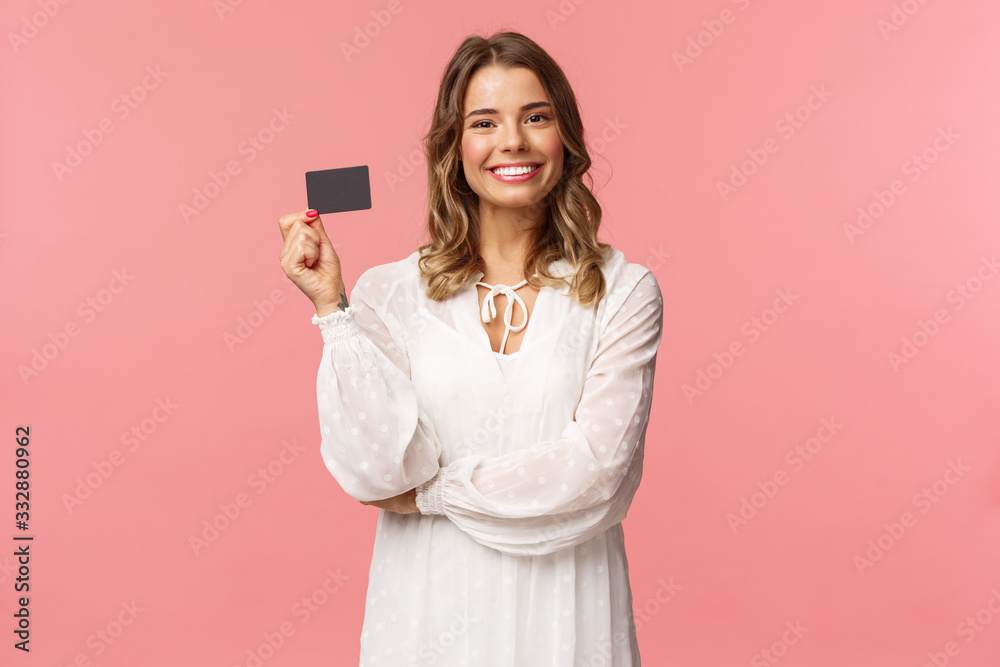 Fototapeta Portrait of pleased good-looking blond european female in white dress, show credit card with satisfied expression, smiling camera, recommend bank services, use payment online, pink background