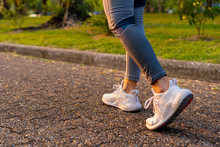 Young Woman Walking Exercise On A Brown Street With White Shoes Exercising
