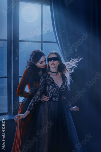 Fotografía Wicked insidious medieval witch red long velvet dress seduces cute beautiful princess in black mask