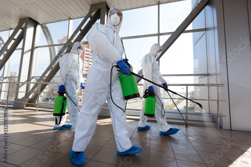 Obraz Men in respirators and protective suits cleaning public places with chemicals - fototapety do salonu