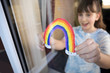 Girl Putting Picture Of Rainbow In Window At Home During Coronavirus Pandemic To Entertain Children