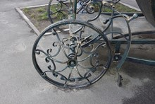 An Iron Wheel With A Forged Pattern On A Decorative Wagon Stands On Gray Asphalt On The Street