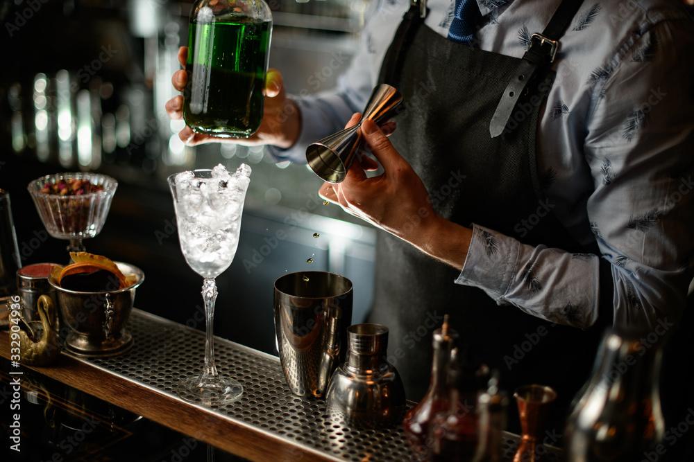 Fototapeta bartender in black apron begins to prepare green alcoholic cocktail
