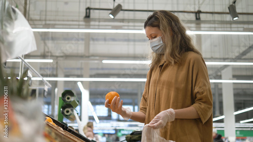 Fototapeta Woman in a medical mask and gloves selects oranges in a grocery supermarket. Protection from the coronavirus epidemic, increased immunity with fresh fruit. obraz