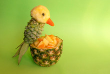 Sliced Fruits In Pineapple Bowl Decorated With Parrot Carved From A Pineapple On Green Background With Copy Space. Food Art, Food Humor And Carving. Pineapple's Parrot Bird