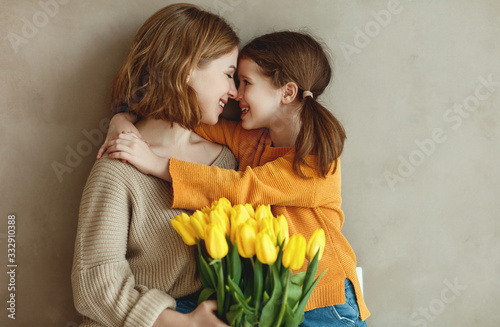Obraz child daughter   gives mother   bouquet of flowers  yellow tulips. - fototapety do salonu