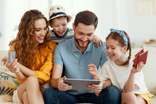 Smiling Parents With Kids Gathering On Sofa Using Tablet While Picking Tour Online Anticipating Summer Vacation All Together.