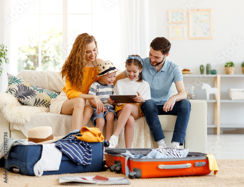 Photo Excited family using tablet on sofa while packing for journey.