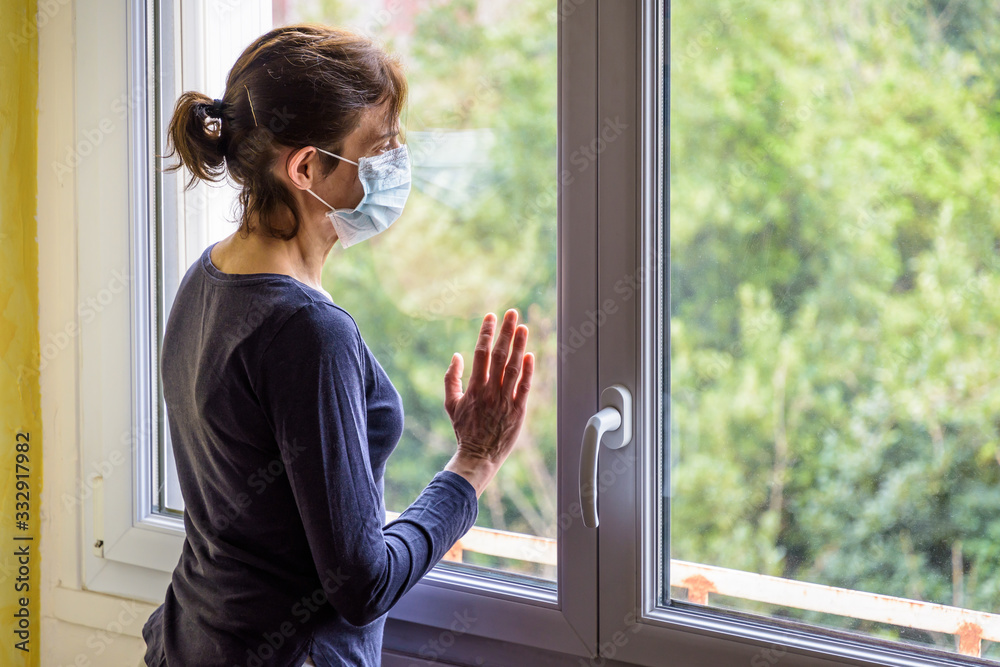 Fototapeta A woman under quarantine at home, wearing a medical face mask and a casual outfit, is standing idle in front of a closed window, the hand on the glass, staring into space.