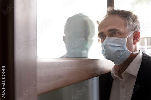 Valokuva Uomo con mascherina chirurgica attraversa la porta di casa con aria preoccupata