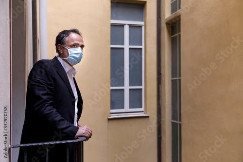 Photo Uomo con mascherina chirurgica si affaccia al balcone con aria sconsolata, sullo