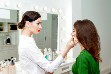 Make-up artist applying powder.