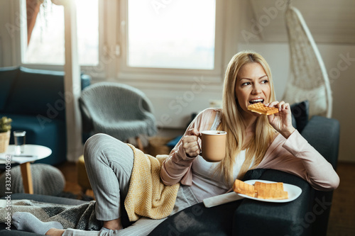 Fototapeta Young woman eating waffles and drinking coffee while relaxing at home. obraz