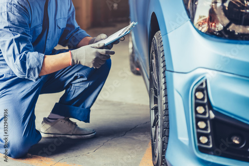 Fotografiet Asian car mechanic technician holding clipboard and checking to maintenance vehicle by customer claim order in auto repair shop garage