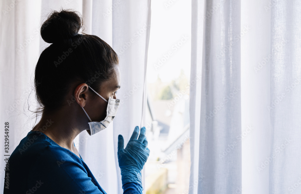Fototapeta fearful woman in corona quarantine looking out of window to the street