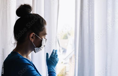 fearful woman in corona quarantine looking out of window to the street