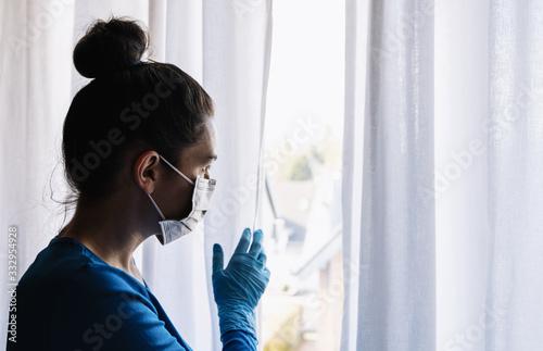 Cuadros en Lienzo fearful woman in corona quarantine looking out of window to the street