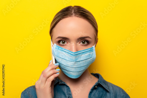 young woman in medical mask talking on smartphone on yellow background