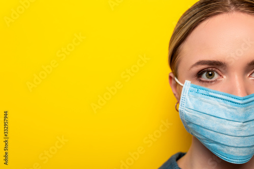 cropped view of young woman in medical mask on yellow background, coronavirus concept