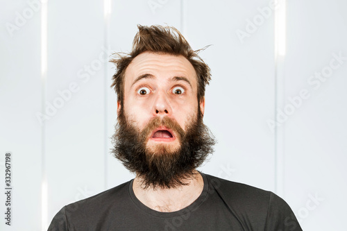 Obraz Portrait freak bearded shaggy surprised man with long hair before haircut in barbershop with open mouth and wide eyes - fototapety do salonu