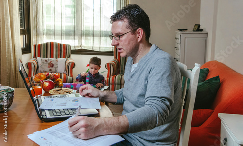 Obraz Father working at home while her son plays - fototapety do salonu