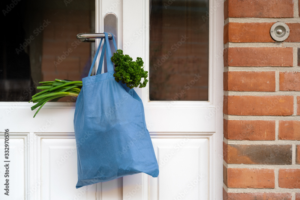 Fototapeta Blue shopping bag with fresh vegetables and goods was hanged on the front door, help concept during quarantine time because of coronavirus infection, copy space, selected focus